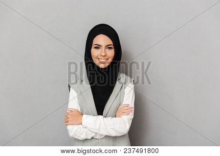 Portrait of a happy young arabian woman standing with arms folded and looking at camera isolated over gray background