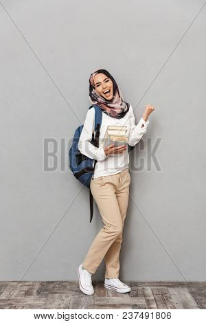 Full length portrait of a smiling young arabian woman student with backpack holding books and celebrating isolated over gray background