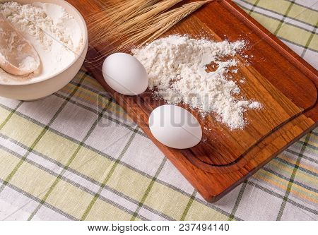 Flour, Eggs And Ears Of Wheat On A Cutting Board And A Wooden Bowl With Flour On A Table