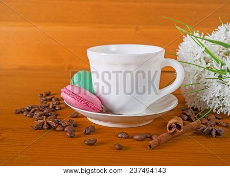 Cup With Coffee, Cakes On A Plate, White Flowers, Grains Of Coffee And Cinnamon On A Wooden Backgrou