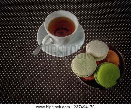 White Cup With Tea And A Bowl With Macarons On The Table
