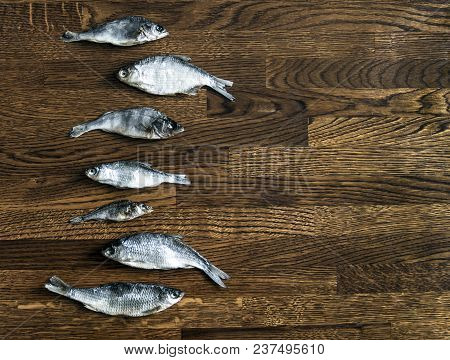 On A Wooden Background Of Small Dark Brown On The Side Lie Salted Dried Fish