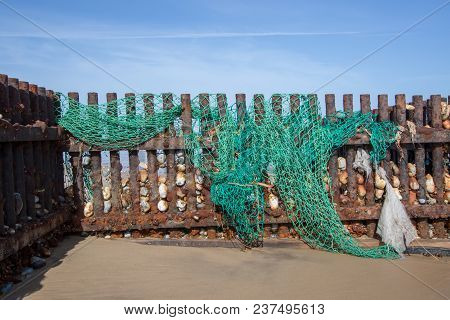 Discarded nylon plastic fishing net. Evironmental sea pollution threat to wildlife washed up on the beach. Tangled green netting. poster