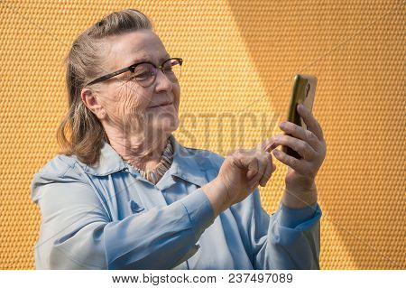 Portrait Of Old Lady, Grandmother Makes Selfie Outdoors At Sun Day. Modern Caucasian Granny Finger