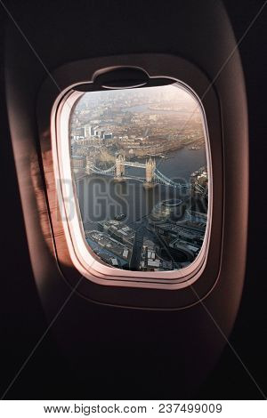 aerial view of London city centre with Tower Bridge and City Hall seen through an airplane window