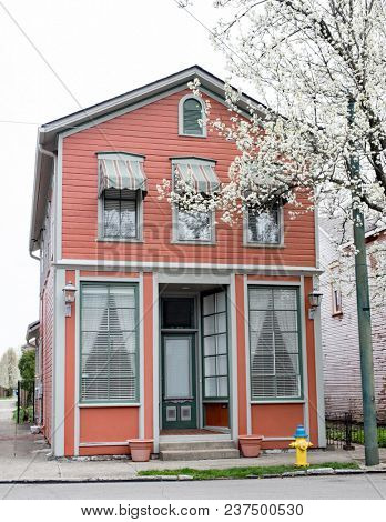 Narrow, Salmon-colored, Store Front House in Spring