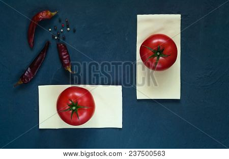 Red Tomatoes Lie On The Plates Of Dough For Lasagna On A Dark Background With Spices, Close-up, Top