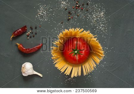 Spices And Fresh Red Tomato Surrounded By Spaghetti On A Dark Background   With Sea Salt, Close-up,