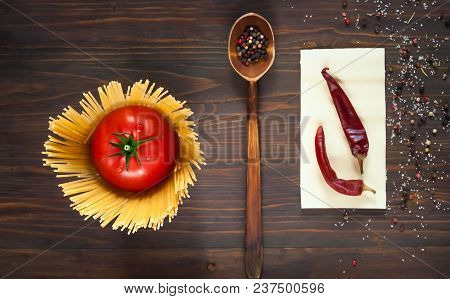 Wooden Spoon With Spices And Fresh Red Tomato, Surrounded By Spaghetti On A Wooden Background, Close