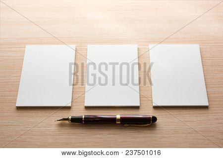 poster of Three white paper blank memo pads next to each other with a brown handle fountain pen beneath. For your message.