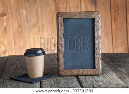 coffee paper cup with vintage slate chalk board, on grunge wood table,