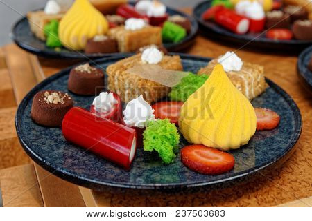 Plates with different sweets on table, close-up