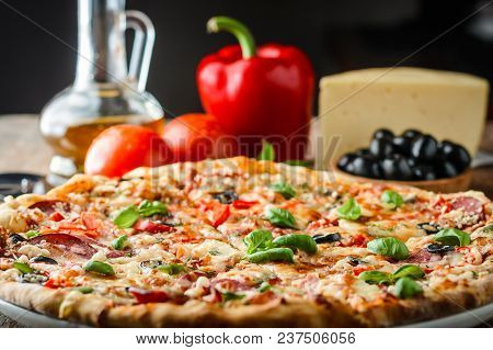 Cooked Pizza And Ingredients On A Table On Dark Background