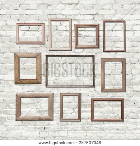 old photo frames on brick wall