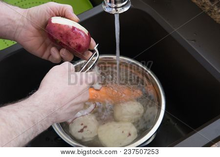 Mans Hands Peeling Organic Potatoes Under Running Water.