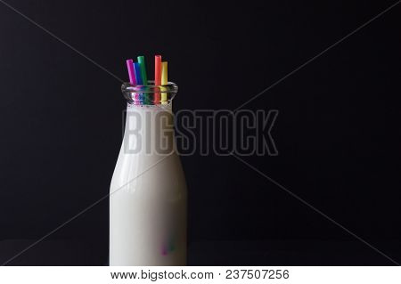 Horizontal Image Of A Glass Jug Filled With White Milk With Coloured Drinking Straws  On A Black Bac