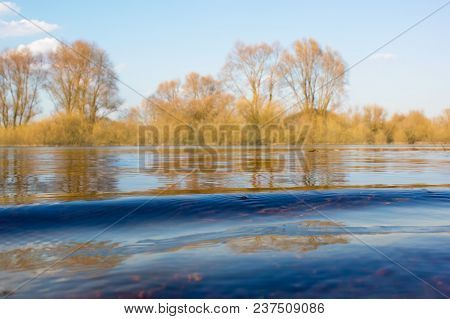 Close-up Of A Small Wave On A River. Various Reflections Of Trees And Bushes On The Shore. A Small R
