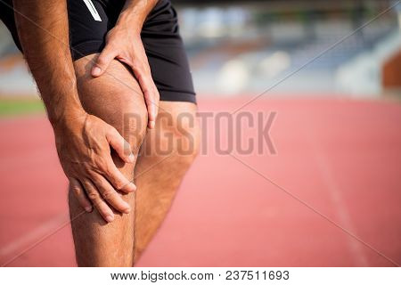Knee Injuries. Young Sport Man With Strong Athletic Legs Holding Knee With His Hands In Pain After S