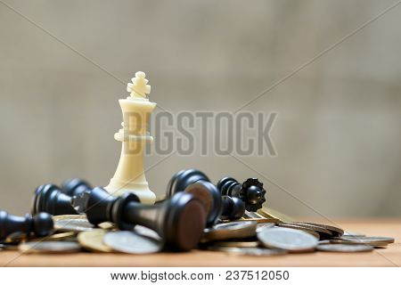 A King Chess Is Placed On A Pile Of Coins.using As Background Business Concept And Strategy Concept
