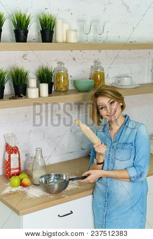Young Attractive Girl Is Preparing Cookies In The Kitchen. She Is Holding A Rolling Pin And Pastry W