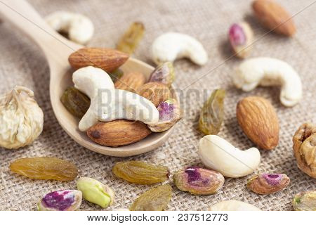 Dried Fruits And Variety Of Nuts Into A Wooden Spoon On The Sackcloth Background, Such As Figs, Almo