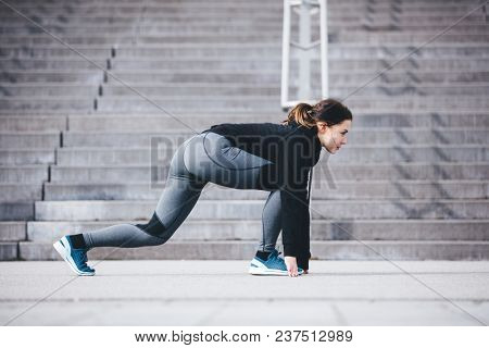Sportswoman in a starting position, ready to run. Active lifestyle. Sport.