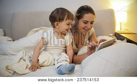 Happy Smiling Mother With Her Toddler Son Playing On Digital Tablet In Bed At Night
