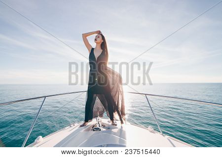 Stylish Young Girl In Black Summer Clothes Is Standing On Her White Yacht, Enjoys Sea Voyage