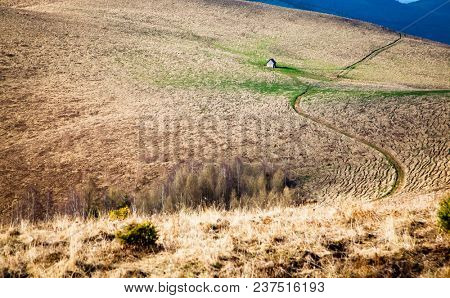 wooden cottage in a vast landscape on a hill