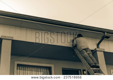 Rear View Of Technician Installing Surveillance Camera On Roof