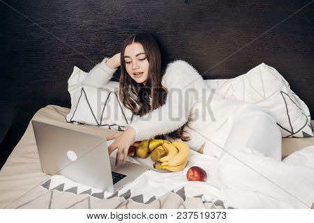 Cute Young Girl With Long Hair Lies In Bed, Resting, Watching Film On Her Laptop And Eating Fruit