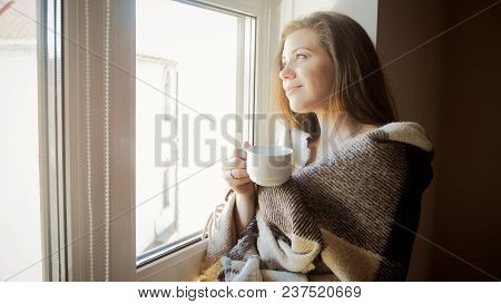 Portrait Of Smiling Young Woman In Plaid Looking Out Of Window