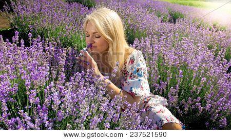 Closeup Portrait Of Blonde Woman Smelling Lavender Flowers In Field
