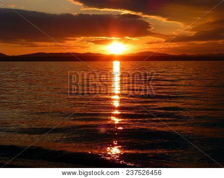 A Beautiful Sunset Over The Lake. Red Sky, Sun, Clouds And Waves. The Mountains On The Horizon In Wh
