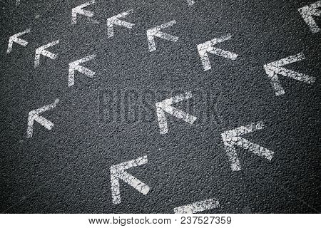 Directional arrows painted on a cement floor.