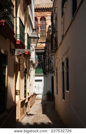 Empty narrow street of the old historical center in Sevilla, Spain