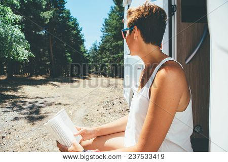 Close Up Of A Young Woman Is Reading A Book Sitting On A Caravan Door Step Parked On A Forest On A H