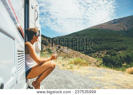 Side View Of A Young Woman Is Sitting On A Caravan Step And Holding A Cup On A Holiday Adventure Tri