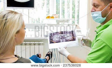 Satisfied Dentist Showing X-ray Image Of Perfect Teeth To His Patient