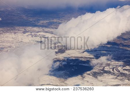 Snowy mountains background and white clouds. Aerial photo from plane's window.