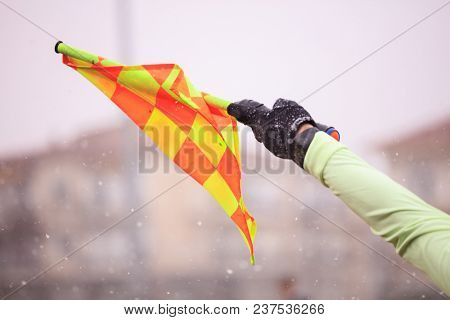 Soccer football referee assistant raises the flag. Blurred snowy background, close up view.
