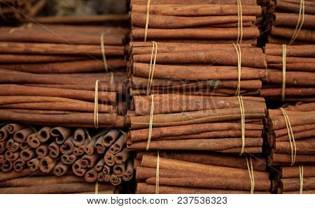 Cinnamon herbal sticks on tied rolls. Canella natural brown aromatic spice background, top view,