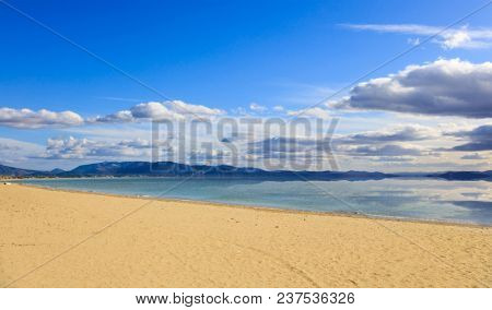Sandy beach, calm sea, blue sky with few white clouds background. Summer destination for holiday and relaxing. Reflection on sea of clouds and mountains.