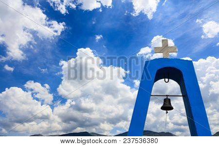 Church's steeple in Greece. Cross on top and bell under it. White clouds on blue sky over mountains background, copyspace