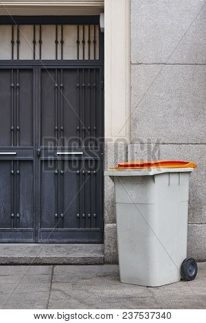 Garbage Can On An Urban Building Entrance Door. Clean Environment