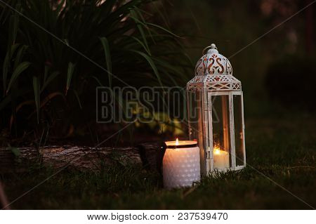 Cozy Evening Garden Scene With Vintage Lantern And Candle Holder With Lawn And Flowers On Background