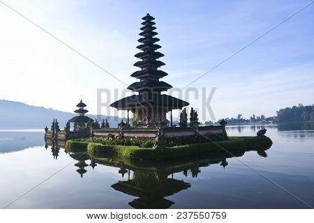 Man On Boat Pura Ulun Danu Water Temple On Lake Brataan Near Bedugal, Bali, Indonesia