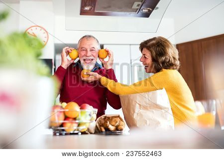 Senior Couple Unpacking Food In The Kitchen. An Old Man And Woman Inside The House, Having Fun.