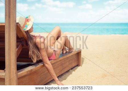 Young Woman Whit Sun Hat Relaxing On Sun Bad Enjoys Sunbath At The Beach With The Sea And Horizon In