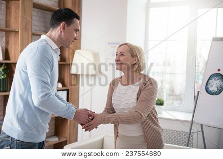 First Meeting. Jolly Senior Woman And Man Grinning While Shaking Hand